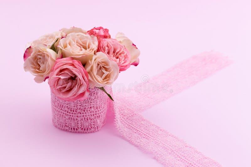 Un mazzo di belle rose sta in un piccolo secchio su un nastro del pizzo su un fondo rosa con spazio per testo fotografia stock libera da diritti
