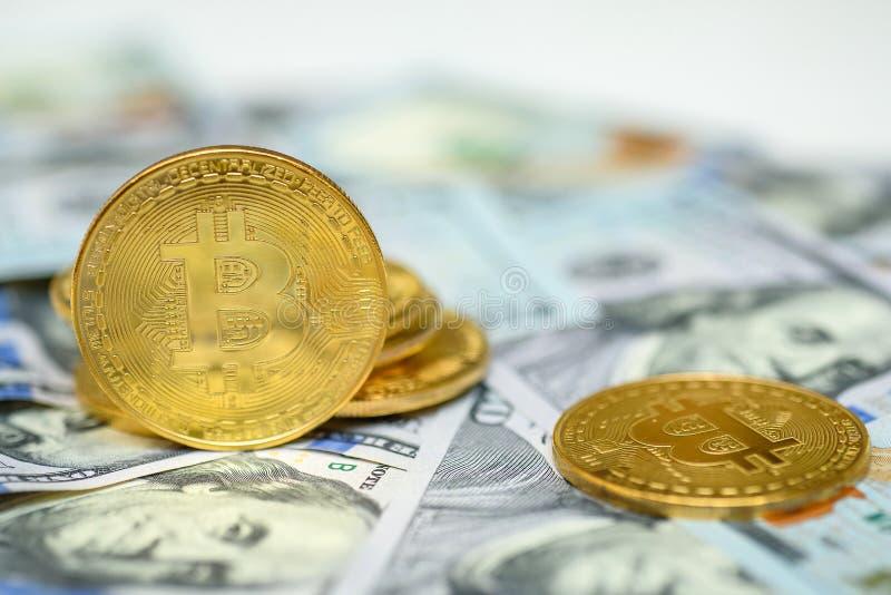 Un mazzo di bitcoin dell'oro conia la stenditura oltre cento fondi delle banconote in dollari fotografia stock libera da diritti