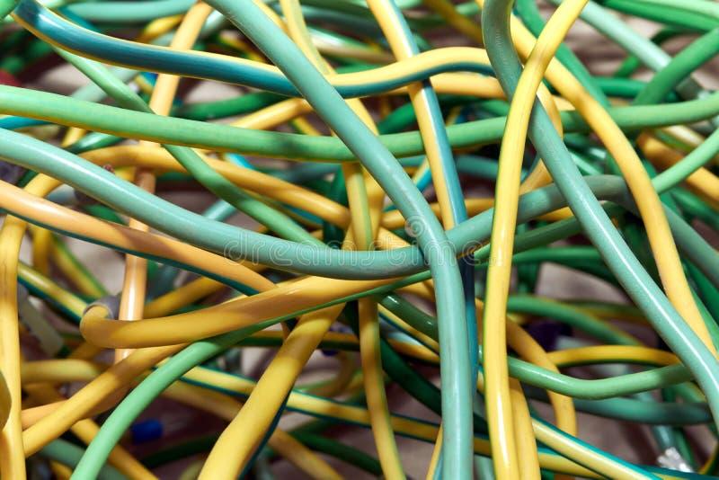 Un mazzo di cavi o di funi giallo verde elettrici attraversati a vicenda fotografia stock