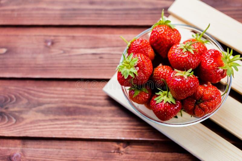 Un mazzo di fragole mature del succo in una ciotola sulla tavola di legno Merce nel carrello fresca delle fragole, frutti appena  fotografia stock