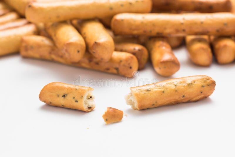 Un mazzo di grissini croccanti con i semi di papavero con un bastone rotto nella priorità alta fotografie stock libere da diritti