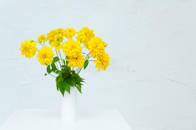 Un mazzo di Heliopsis giallo dei fiori in un vaso bianco Nella sala su un'apprettatrice bianca fotografie stock libere da diritti