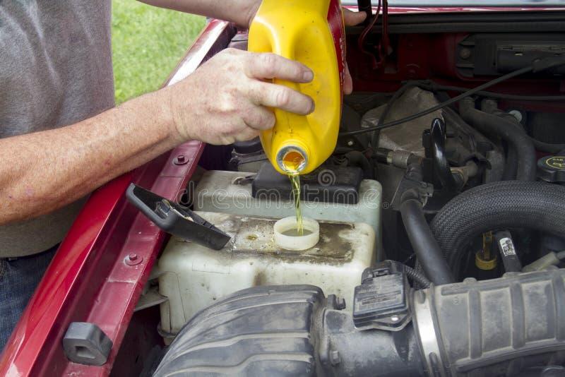 Un mecánico Adding Coolant To un camión más viejo fotos de archivo libres de regalías