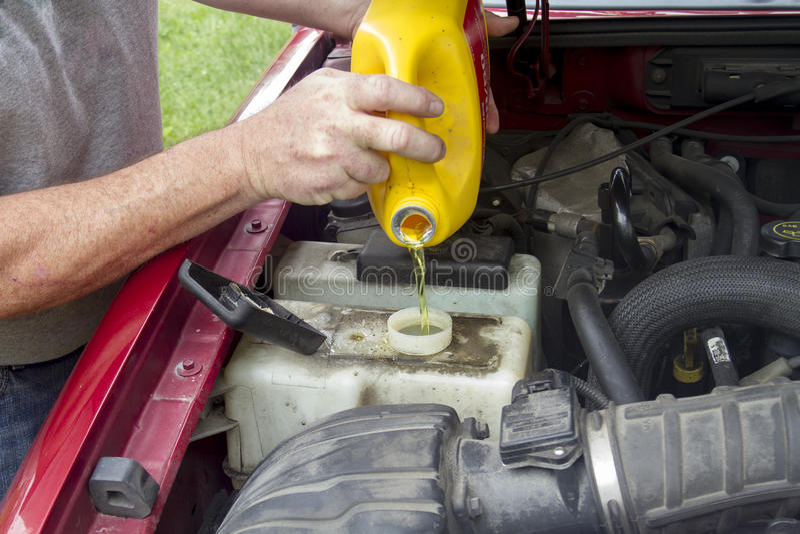 Un meccanico Adding Coolant To un più vecchio camion fotografie stock libere da diritti