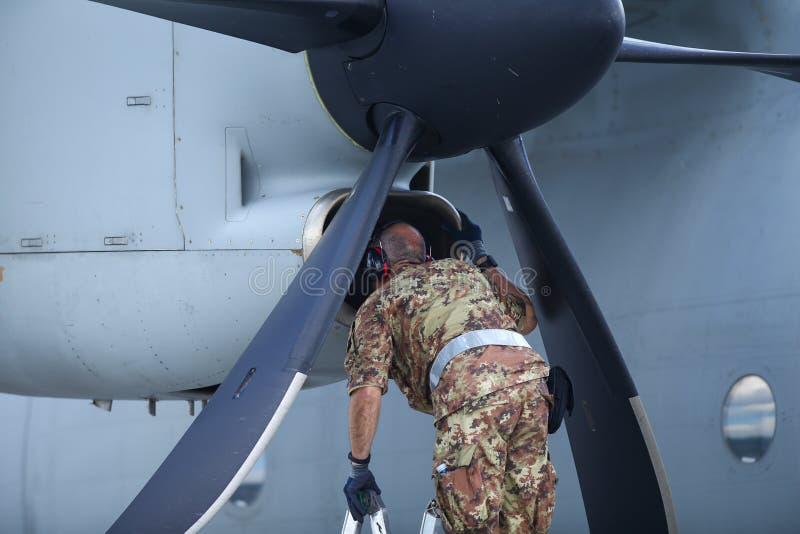 Un meccanico sta ispezionando le parti di un aereo da carico militare spartano Alenia C-27J dopo l'atterraggio su una base aerea immagini stock libere da diritti