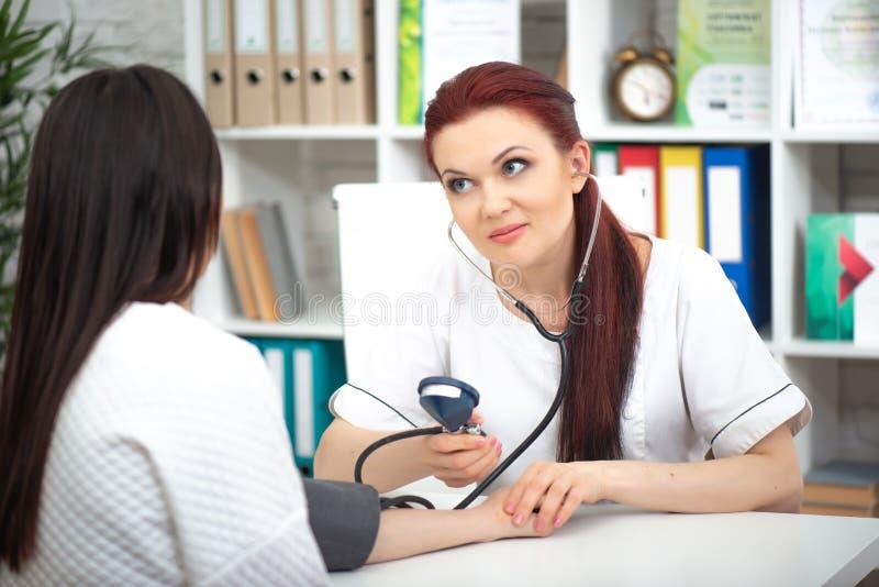 Un medico amichevole sorridente prende un paziente nel suoi ufficio e pressione delle misure La donna esprime il parere medico immagine stock libera da diritti