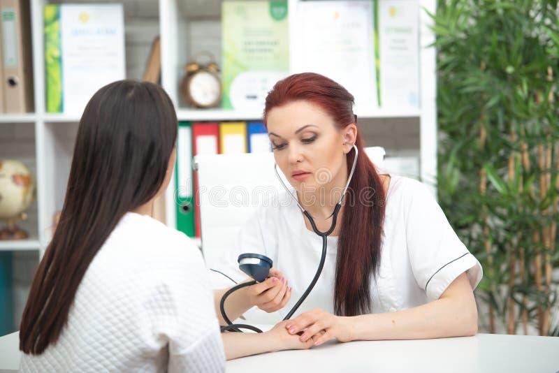 Un medico amichevole sorridente prende un paziente nel suoi ufficio e pressione delle misure La donna esprime il parere medico fotografie stock libere da diritti