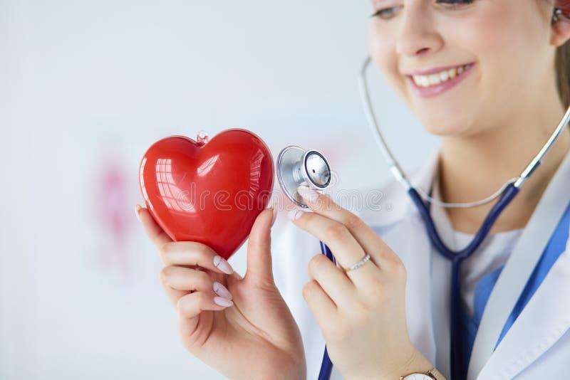 Un medico con lo stetoscopio che esamina cuore rosso, su bianco fotografia stock