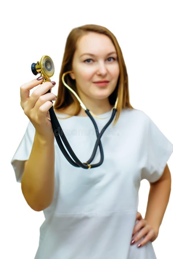 Un medico femminile con uno stetoscopio isolato su fondo bianco Donna sorridente di medico con lo stetoscopio a disposizione immagine stock libera da diritti
