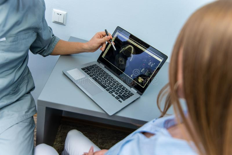 Un medico maschio e un paziente della ragazza stanno sedendo vicino ad un computer portatile e ad una conversazione fotografia stock libera da diritti