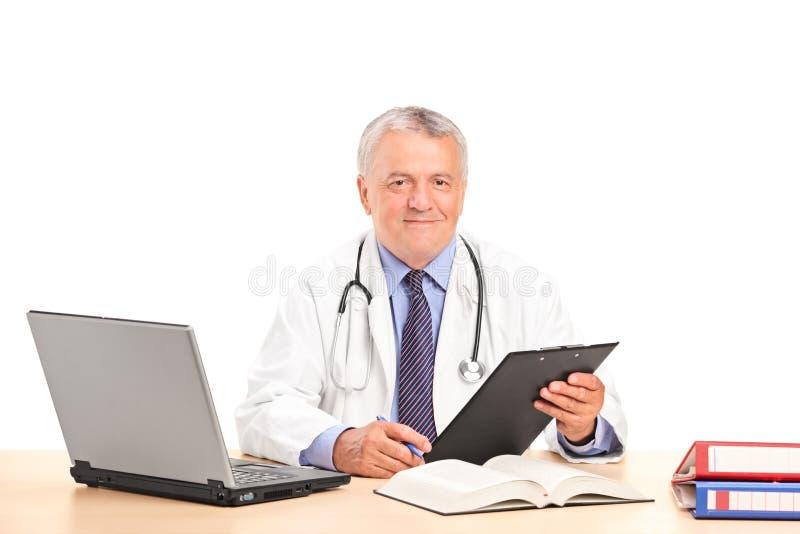 Un medico maturo che propone nel suo ufficio immagini stock libere da diritti