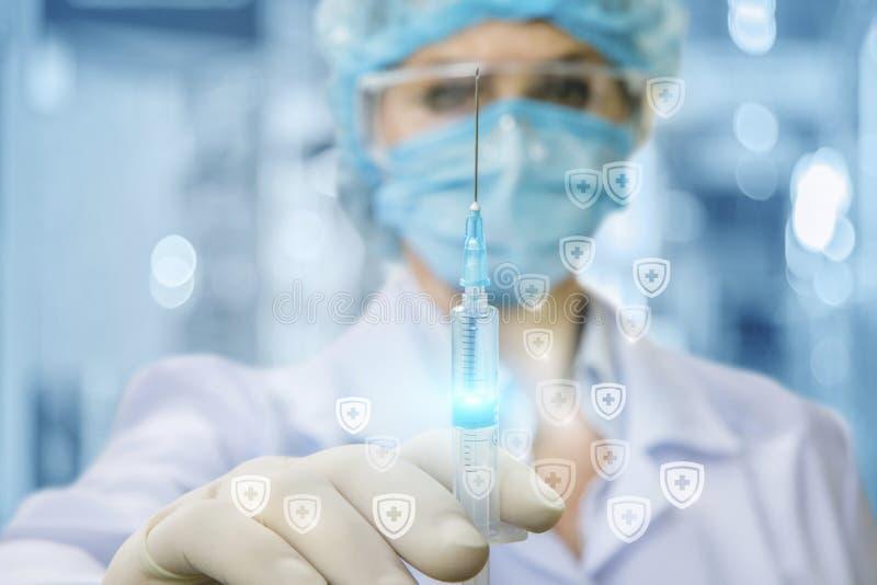 Un medico nella maschera medica sta tenendo una siringa con un certo vaccino in sua mano in guanto di gomma immagini stock