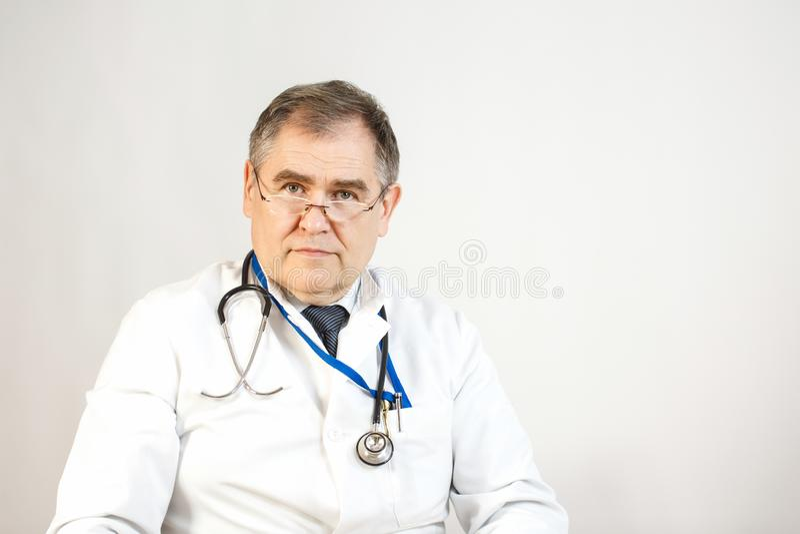 Un medico nelle camice ed in un legame sta guardando in avanti, un whist ha uno stetoscopio e un distintivo sul suo collo e ci so fotografie stock