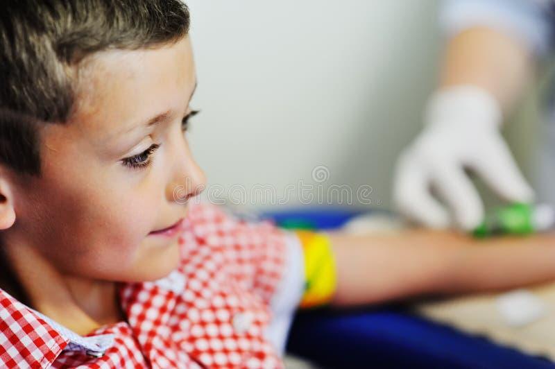 Un medico o un infermiere prende il sangue da una vena in un bambino di un ragazzo immagini stock libere da diritti