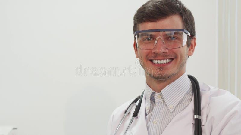 Un medico sorridente mette sopra i vetri trasparenti speciali del laboratorio immagine stock libera da diritti