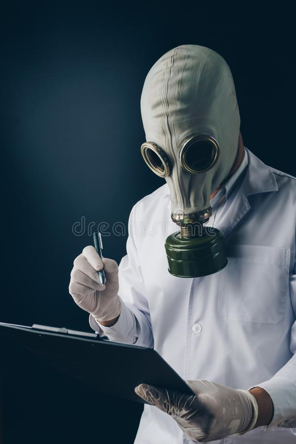 Un medico spaventoso in maschera antigas che tiene una penna e una lavagna per appunti fotografie stock libere da diritti