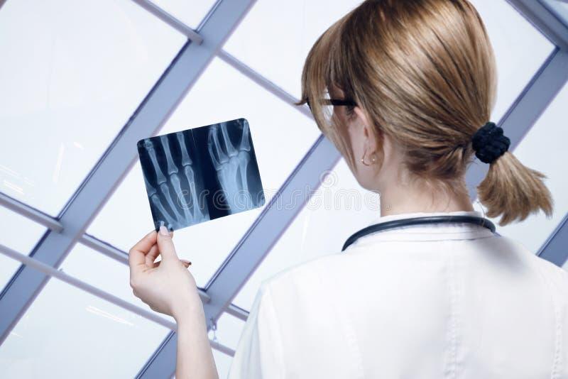 Un medico sta esaminando un'immagine dei raggi x della mano per il trattamento e la diagnosi fotografie stock libere da diritti