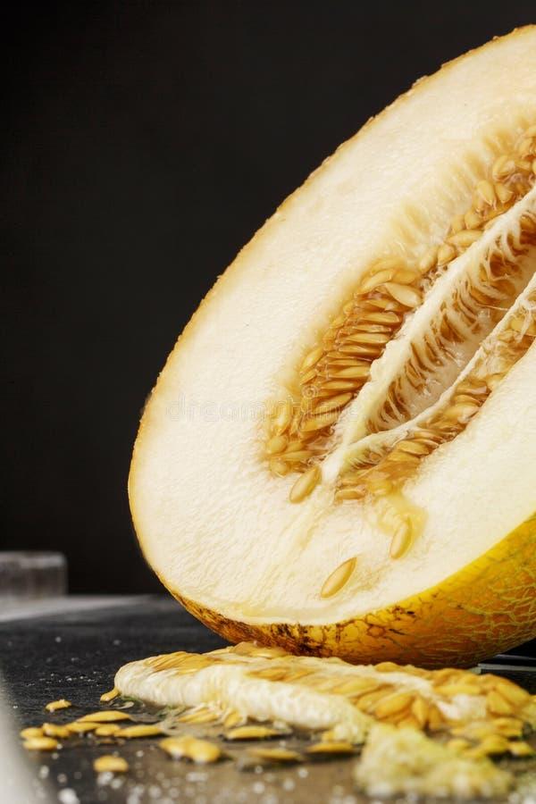 Un melón hermoso y jugoso Una mitad de una pulpa madura en un fondo negro Corte el melón Ingredientes naturales y orgánicos fotos de archivo