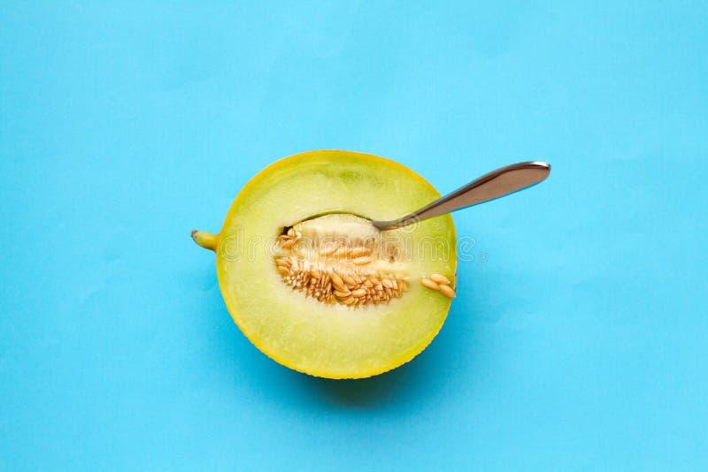 Un melon de miellée juteux et une cuillère images libres de droits