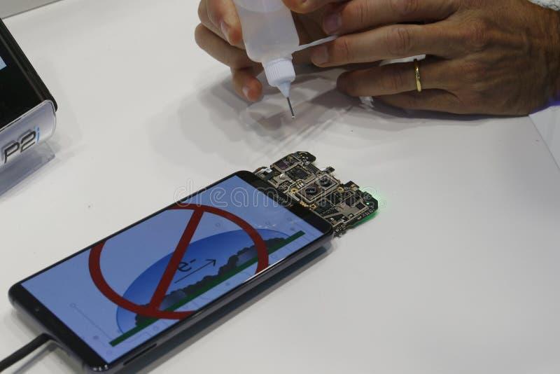 Un membre du personnel montre aux visiteurs comment sceller leurs téléphones portables à MWC19 à Barcelone photographie stock libre de droits