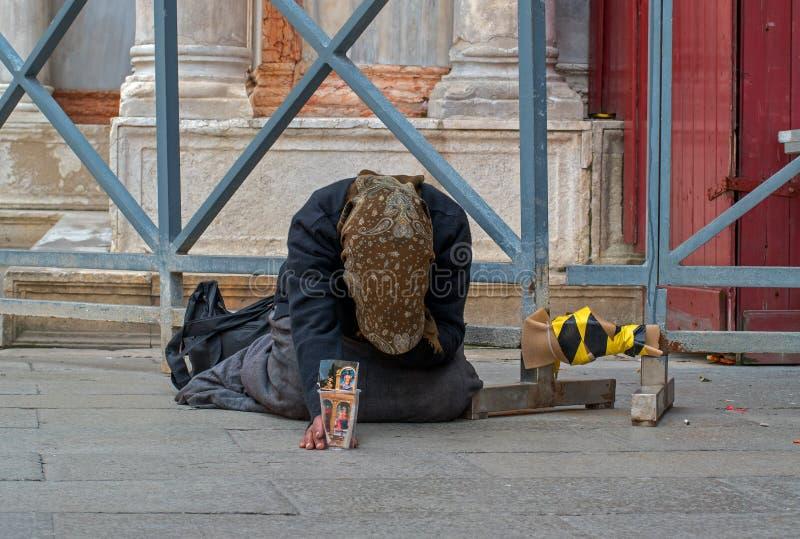 Un mendicante femminile senza tetto sta elemosinando sulla via a Venezia, Italia Una donna del mendicante tiene una tazza del car fotografia stock libera da diritti