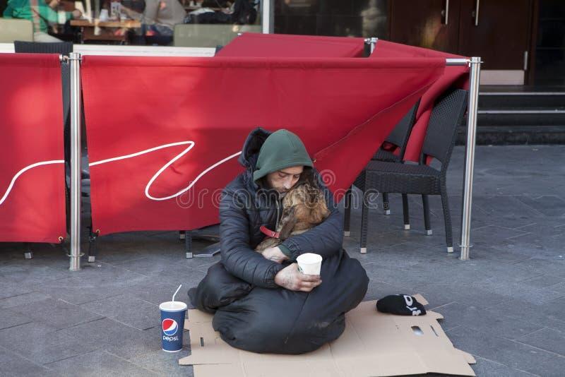 Un mendigo dormido y que sostiene un perro en sus brazos imagen de archivo