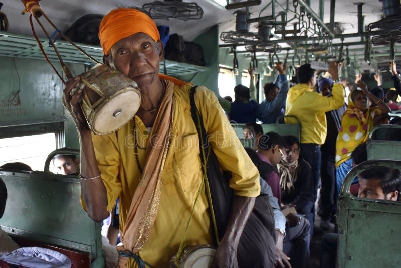 Un mendigo pobre que canta y que pide en un tren local fotos de archivo libres de regalías