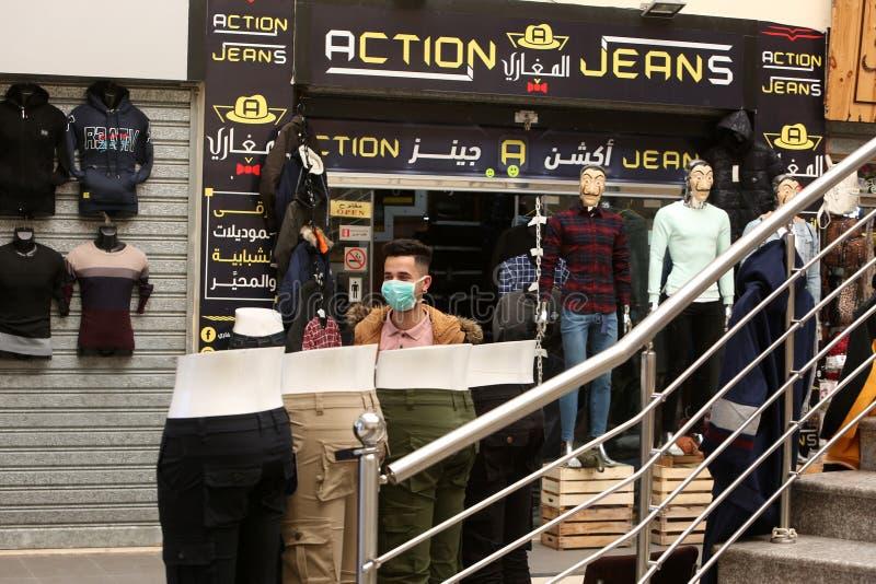 Un mercante palestinese indossa una mascherina per la salute, a causa dei timori di diffusione della malattia del coronavirus COV fotografia stock libera da diritti