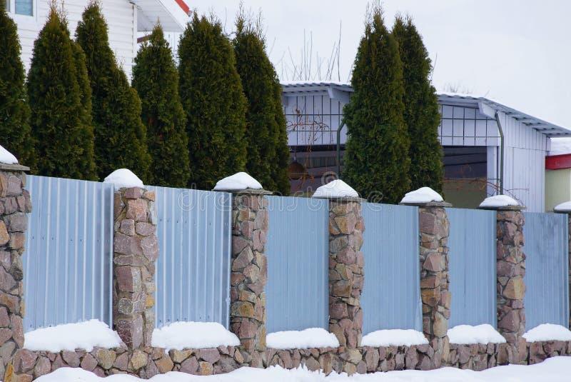 Un metallo grigio e un recinto di pietra sotto neve bianca e una fila delle conifere verdi fotografia stock