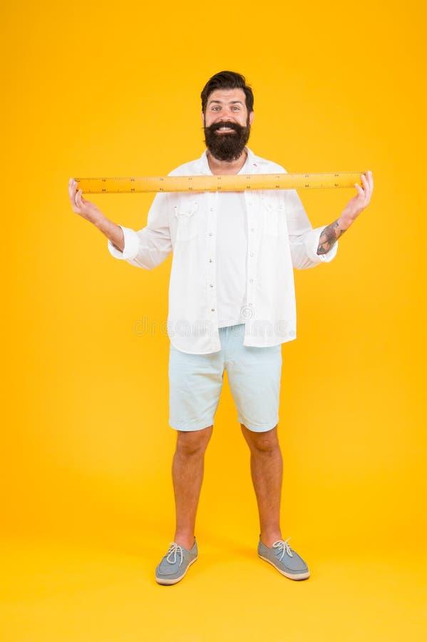 Un metro Regla barbuda de la tenencia del inconformista del hombre Longitud de la medida Clasifique alto y la longitud Tama?o gra imagenes de archivo