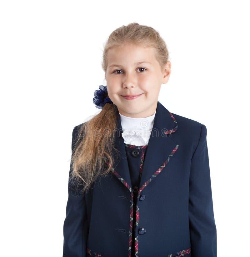 Un mezzo ritratto di lunghezza di sette anni dello studente in uniforme, ragazza dei capelli biondi, ha isolato il fondo bianco fotografia stock libera da diritti