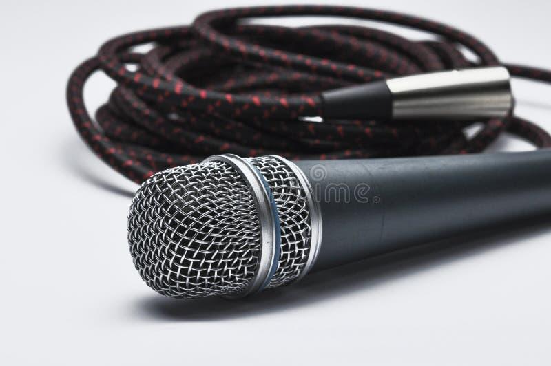 Un microfono con un cavo isolato su un fondo bianco Copi lo spazio fotografie stock