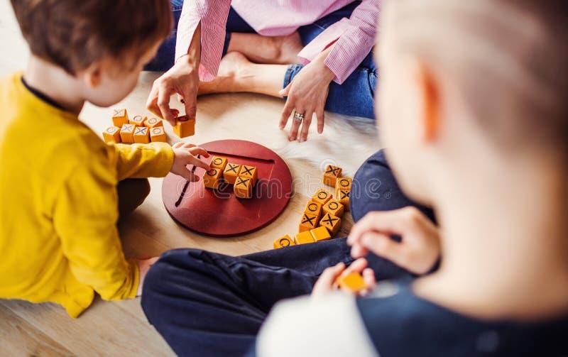 Un midsection de la madre con dos niños que juegan a los juegos de mesa en el piso fotografía de archivo