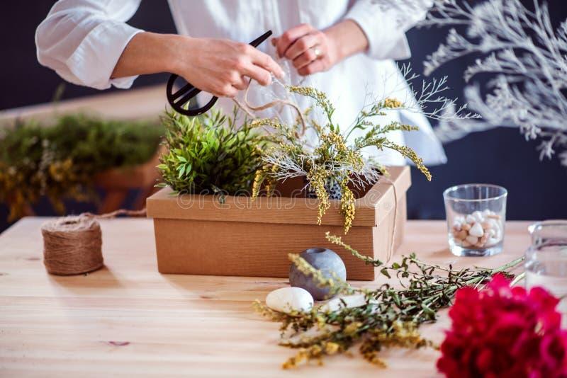 Un midsection de la mujer creativa joven en una florister?a Un inicio del negocio del florista imagen de archivo