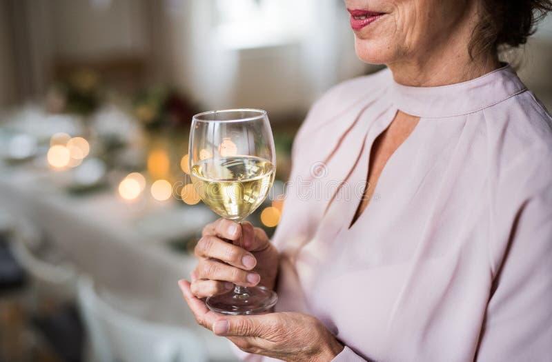 Un midsection de una mujer mayor que se coloca dentro en un sistema del sitio para un partido, sosteniendo el vino fotos de archivo libres de regalías