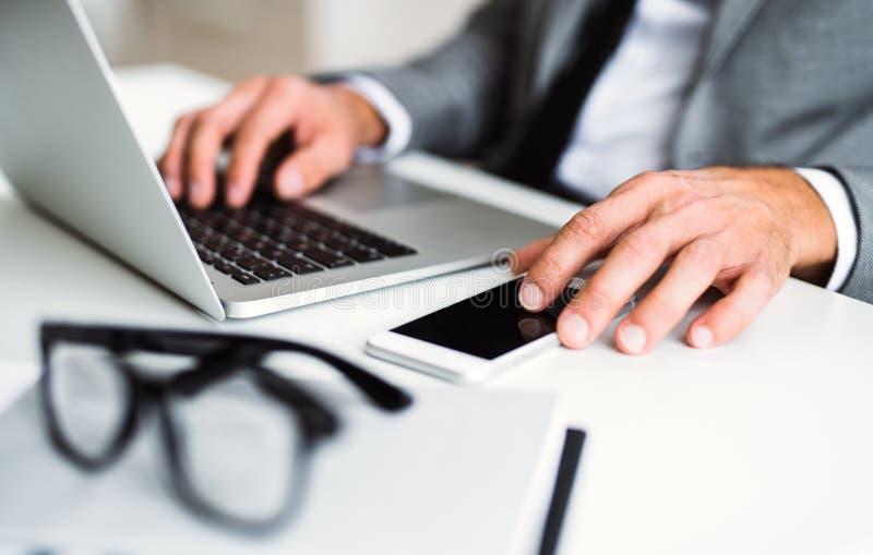 Un midsection del hombre de negocios con smartphone y del ordenador portátil que se sienta en la tabla, trabajando fotografía de archivo