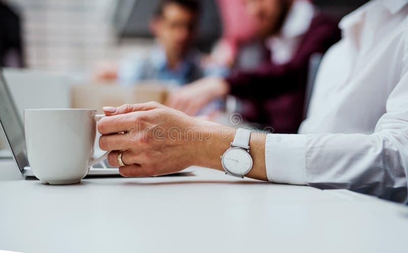 Un midsection della donna di affari con un funzionamento della tazza di caffè nell'ufficio, facendo uso del computer portatile fotografia stock libera da diritti