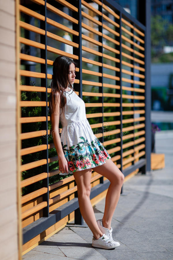 Un mignon, beau et assez femelle dans une robe blanche à la mode sur la rue La femme avec du charme pose sur le fond en bois image libre de droits