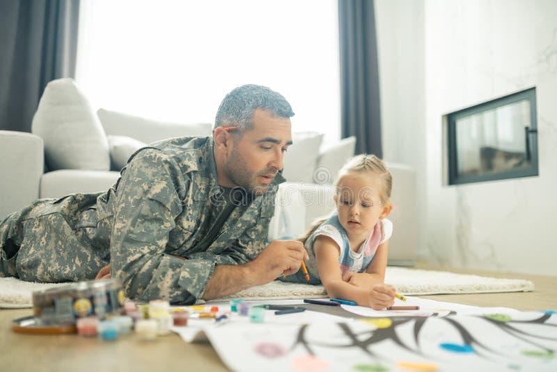 Un militaire peint un arbre de famille avec sa jolie fille photo libre de droits