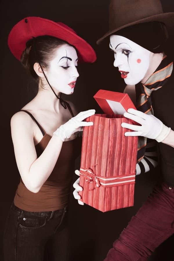 Un mimo dell'uomo dà un regalo ad una donna fotografia stock