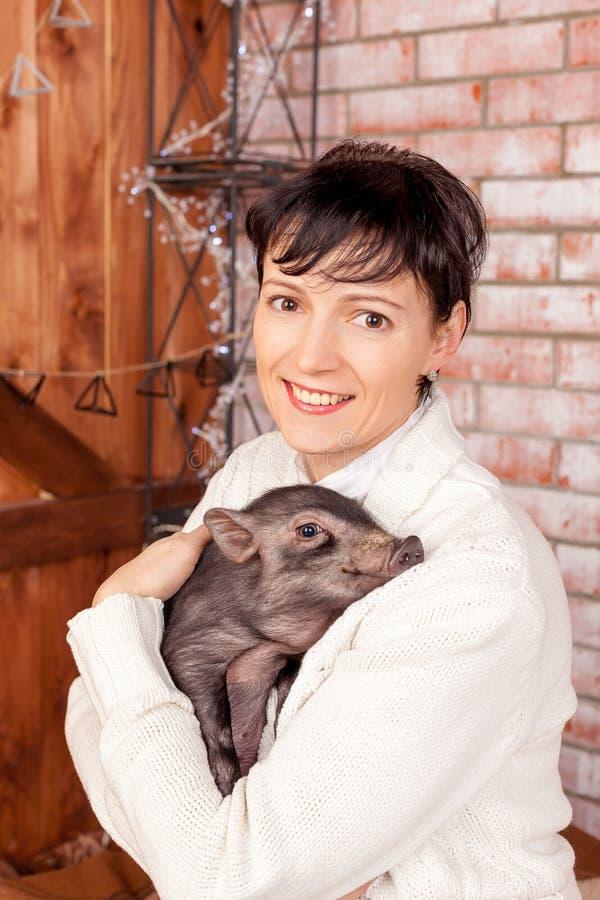 Un mini-cerdo del bebé y una mujer hermosa cerca del árbol de navidad, simbolizando los 2019 Años Nuevos próximo, año de un cerdo fotos de archivo libres de regalías