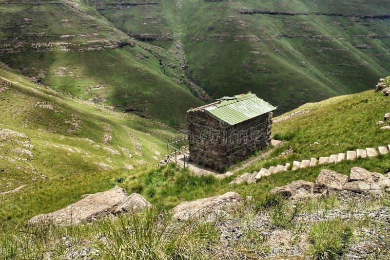 Un minuscule bâtiment jouxte un abîme abrupt dans les montagnes du Drakensberg au Lesotho et en Afrique du Sud photo stock