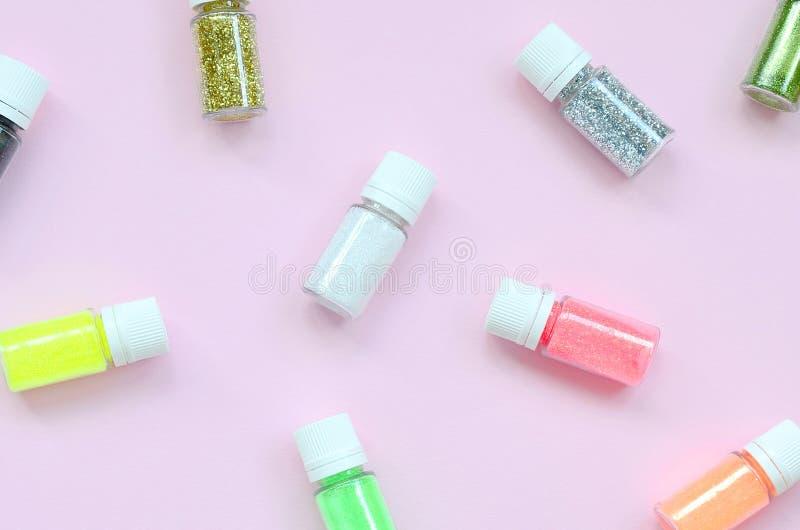Un modèle étendu plat avec les bouteilles colorées de scintillement se trouve sur le fond rose en pastel photo libre de droits