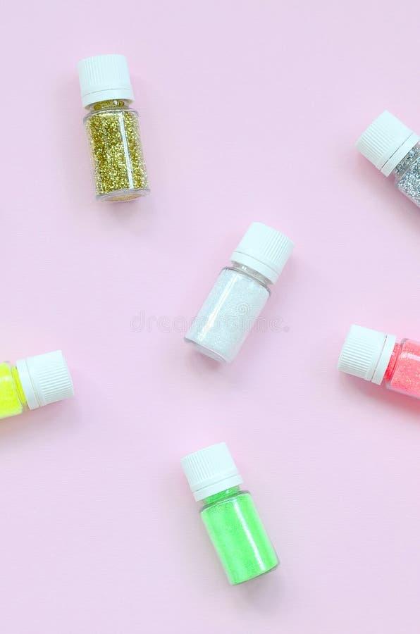 Un modèle étendu plat avec les bouteilles colorées de scintillement se trouve sur le fond rose en pastel photographie stock libre de droits