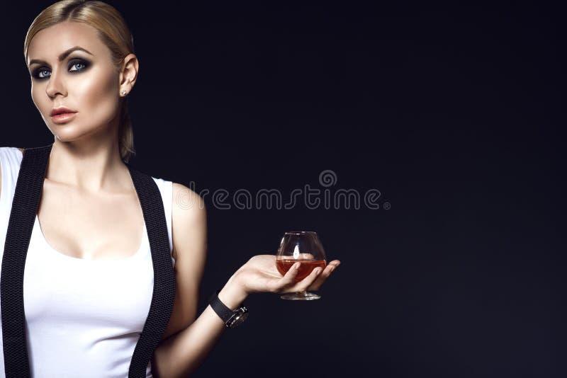 Un modèle blond avec retirés les cheveux et l'oeil fumeux préparent le dessus blanc de port avec des bretelles tenant un verre d' photographie stock libre de droits