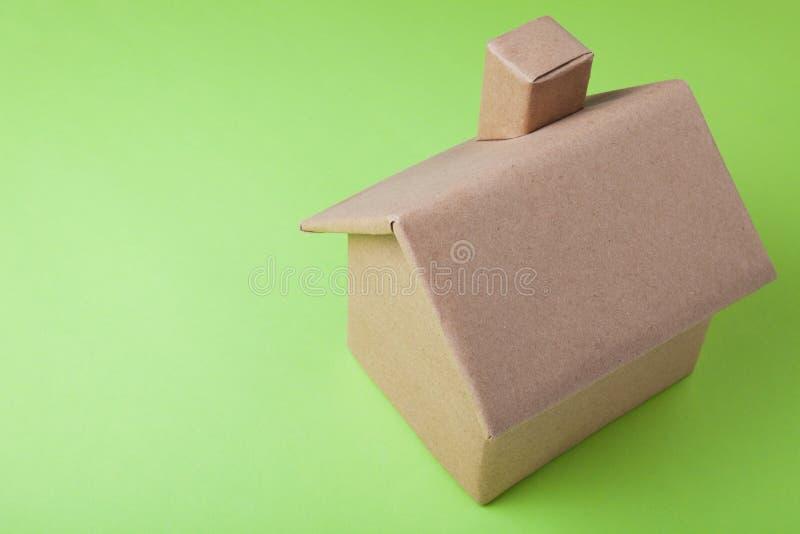 Un modèle d'une maison de carton sur un fond vert photographie stock libre de droits