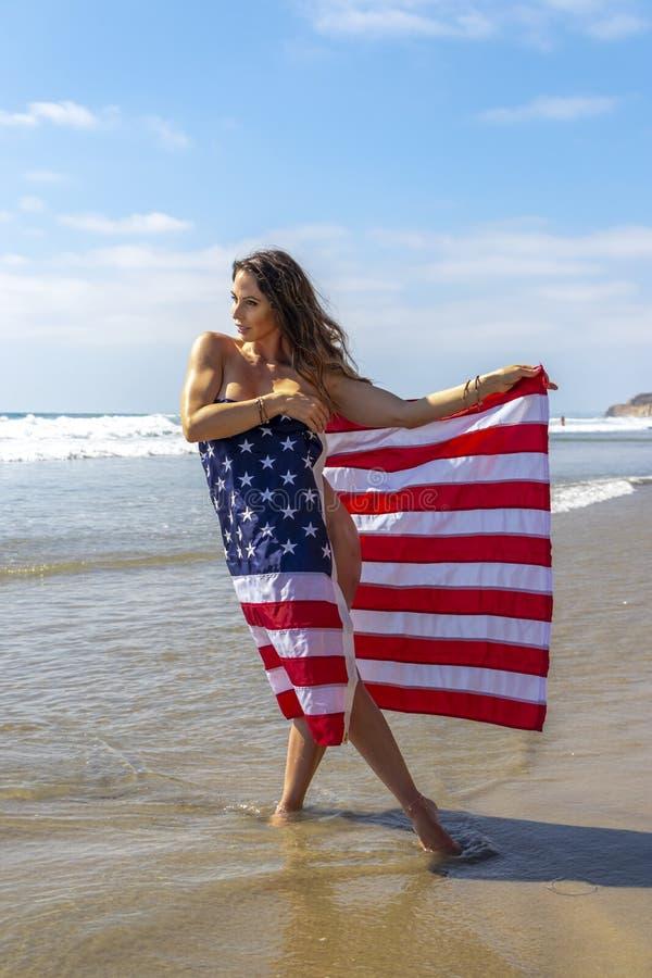 Un modello castana adorabile Poses Nude At la costa con una bandiera americana fotografia stock libera da diritti
