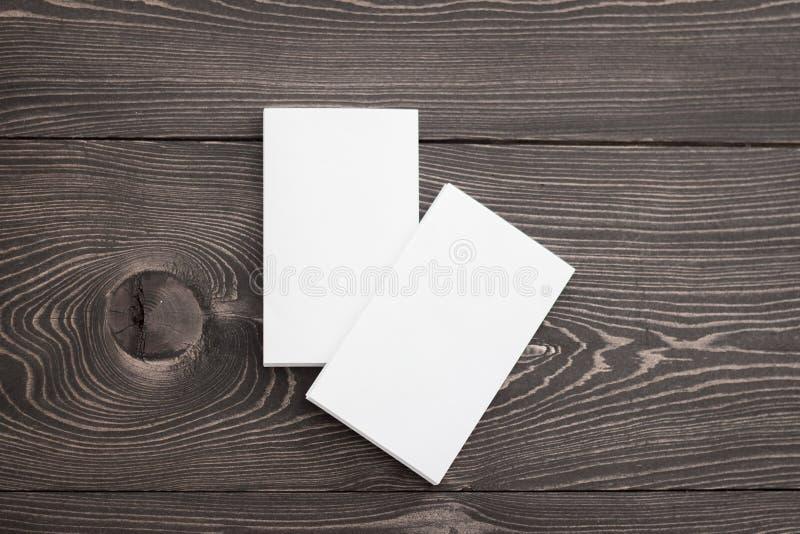Un modello del primo piano di due pile bianche dei biglietti da visita a fondo di legno marrone Modello per l'identità marcante a fotografia stock
