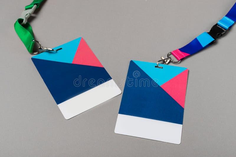Un modello di due distintivi di colore su fondo grigio fotografia stock libera da diritti