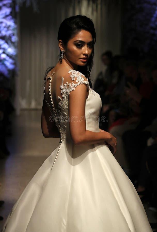 Un modelo camina la pista que lleva los vestidos de Matthew Christopher en la semana nupcial de la moda de NY foto de archivo libre de regalías